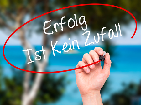 ist: Man Hand writing Erfolg Ist Kein Zaufall (Success Is No Accident in German) with black marker on visual screen. Isolated on background. Business, technology, internet concept. Stock Photo
