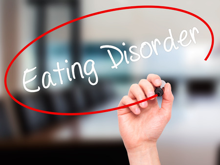 avoidance: Man Hand writing Eating Disorder  with black marker on visual screen. Isolated on background. Business, technology, internet concept. Stock Photo