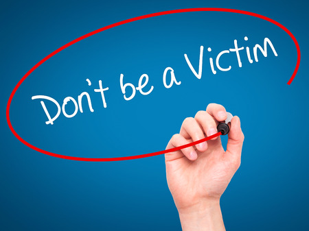 sufferer: Man Hand writing Dont be a Victim  with black marker on visual screen. Isolated on blue. Business, technology, internet concept. Stock Photo