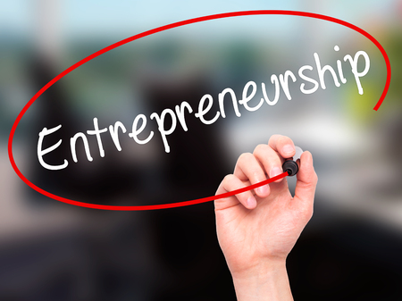 self starter: Man Hand writing Entrepreneurship with black marker on visual screen. Isolated on office. Business, technology, internet concept. Stock Image Stock Photo