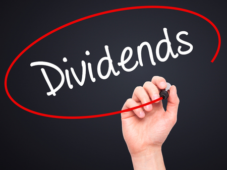 dividends: Man Hand writing Dividends with black marker on visual screen. Isolated on background. Business, technology, internet concept. Stock Photo