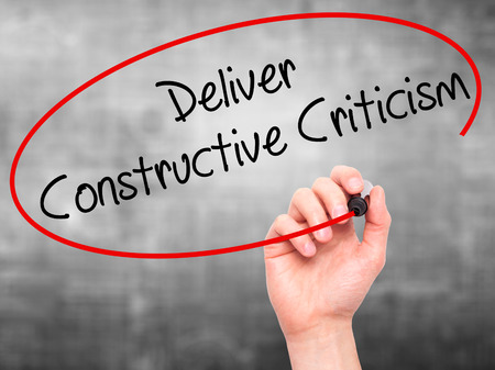 Man Hand writing Deliver Constructive Criticism with black marker on visual screen. Isolated on background. Business, technology, internet concept. Stock Photo