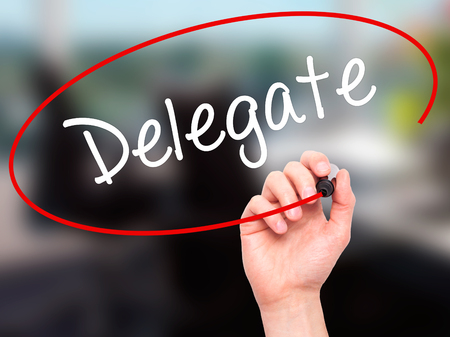 delegar: Hombre de la mano escribiendo Delegado con marcador negro en la pantalla visual. Aislado en la oficina. Negocios, la tecnología, el concepto de internet. Foto de stock Foto de archivo