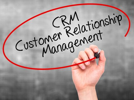 relationship strategy: Man Hand writing CRM Customer Relationship Management  with black marker on visual screen. Isolated on grey. Business, technology, internet concept. Stock Photo Stock Photo