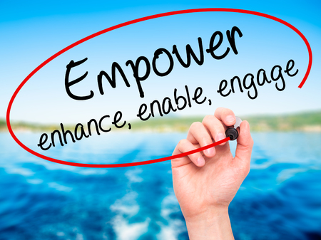 enable: Man Hand writing Empower enhance, enable, engage with black marker on visual screen. Isolated on nature. Business, technology, internet concept. Stock Photo