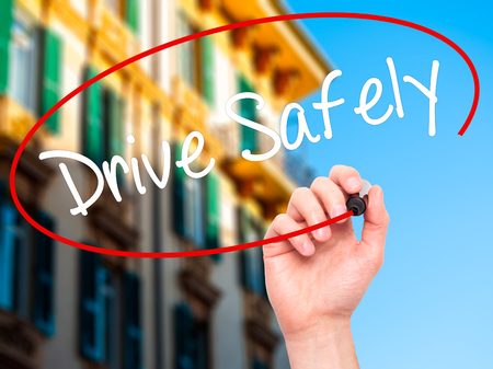 drive safely: Man Hand writing  Drive Safely with black marker on visual screen. Isolated on city. Business, technology, internet concept. Stock Photo