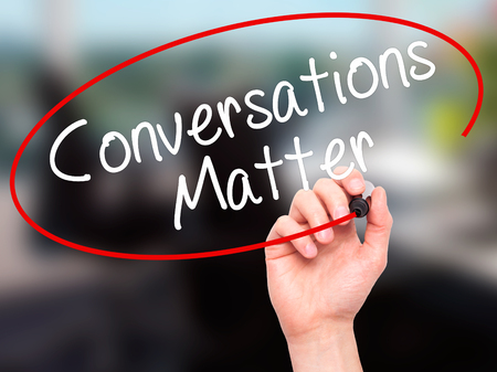 conversing: Man Hand writing Conversations Matter with black marker on visual screen. Isolated on office. Business, technology, internet concept. Stock Image Stock Photo