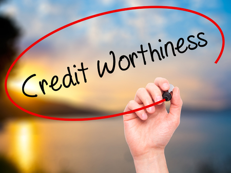 creditworthiness: Man Hand writing Credit Worthiness with black marker on visual screen. Isolated on nature. Business, technology, internet concept. Stock Photo Stock Photo