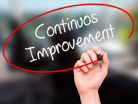 Man Hand writing Continuos Improvement with black marker on visual screen. Isolated on office. Business, technology, internet concept. Stock Photo