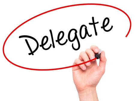 delegar: Hombre de la mano escribiendo Delegado con marcador negro en la pantalla visual. Aislado en blanco. Negocios, la tecnolog�a, el concepto de internet. Foto de stock