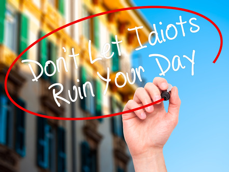 irrelevant: Man Hand writing Dont Let Idiots Ruin Your Day with black marker on visual screen. Isolated on city. Business, technology, internet concept. Stock Photo