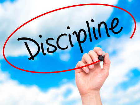 interdependent: Man Hand writing Discipline with black marker on visual screen. Isolated on sky. Business, technology, internet concept. Stock Photo