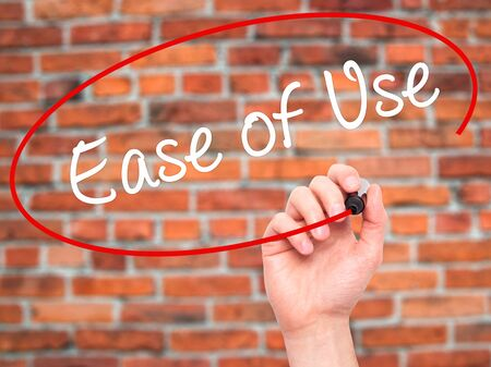 with ease: Man Hand writing Ease of Use with black marker on visual screen. Isolated on bricks. Business, technology, internet concept. Stock Photo