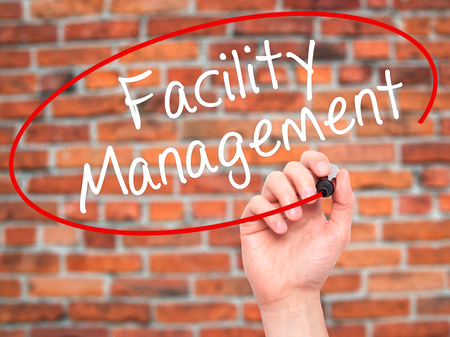 dwell house: Man Hand writing Facility Management with black marker on visual screen. Isolated on bricks. Business, technology, internet concept. Stock Photo Stock Photo