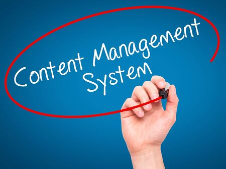 ecm: Man Hand writing Content Management System  with black marker on visual screen. Isolated on blue. Business, technology, internet concept. Stock Photo