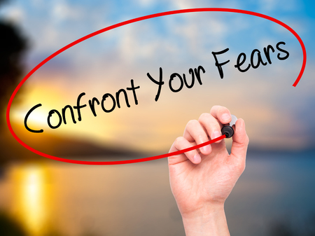 confront: Man Hand writing Confront Your Fears with black marker on visual screen. Isolated on background. Business, technology, internet concept. Stock Photo