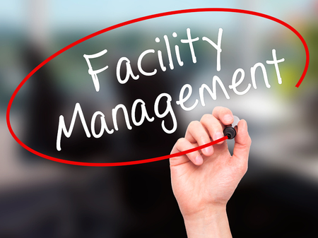 dwell house: Man Hand writing Facility Management with black marker on visual screen. Isolated on office. Business, technology, internet concept. Stock Photo