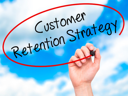 Man Hand writing Customer Retention Strategy with black marker on visual screen. Isolated on sky. Business, technology, internet concept.