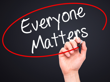 everyone: Man Hand writing Everyone Matters with black marker on visual screen. Isolated on black. Business, technology, internet concept. Stock Photo