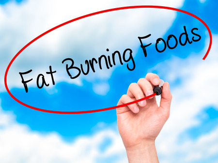 fat burning: Man Hand writing Fat Burning Foods with black marker on visual screen. Isolated on sky. Business, technology, internet concept. Stock Photo