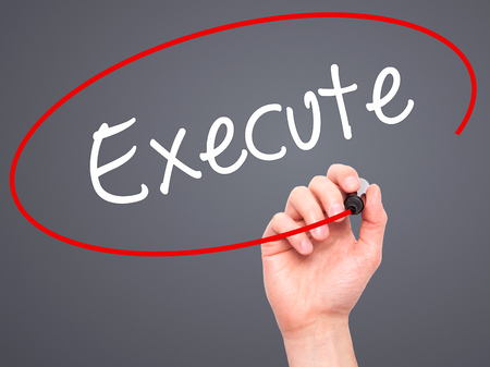 execute: Man Hand writing Execute with black marker on visual screen. Isolated on background. Business, technology, internet concept. Stock Photo