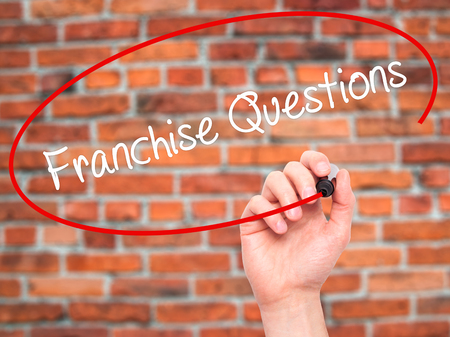 to incorporate: Man Hand writing Franchise Questions with black marker on visual screen. Isolated on bricks. Business, technology, internet concept. Stock Photo