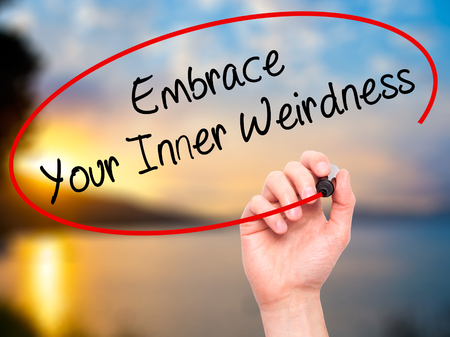 street wise: Man Hand writing Embrace Your Inner Weirdness  with black marker on visual screen. Isolated on nature. Business, technology, internet concept. Stock Photo