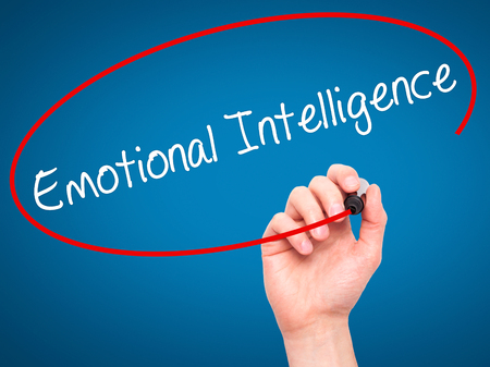 continence: Man Hand writing Emotional Intelligence with black marker on visual screen. Isolated on blue. Business, technology, internet concept. Stock Photo