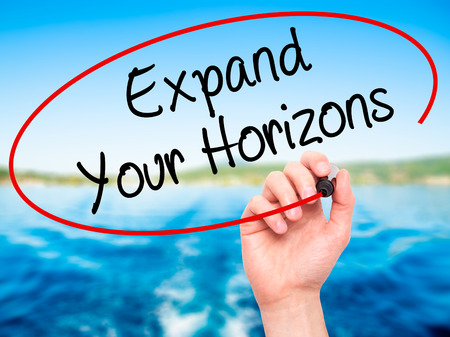broaden: Man Hand writing  Expand Your Horizons  with black marker on visual screen. Isolated on background. Business, technology, internet concept. Stock Photo