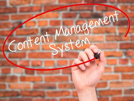 Man Hand writing Content Management System  with black marker on visual screen. Isolated on bricks. Business, technology, internet concept. Stock Photo Stock Photo