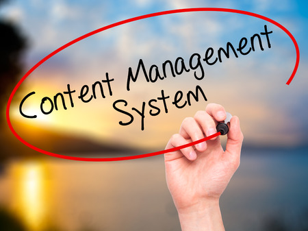 ecm: Man Hand writing Content Management System  with black marker on visual screen. Isolated on nature. Business, technology, internet concept. Stock Photo