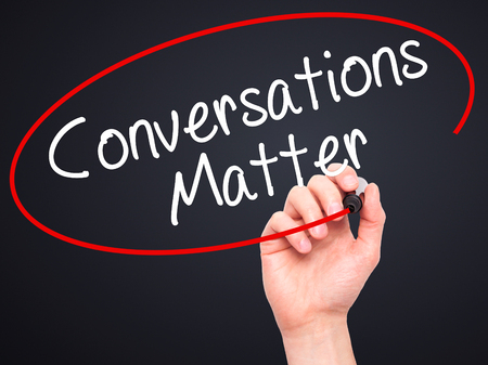 business matter: Man Hand writing Conversations Matter with black marker on visual screen. Isolated on black. Business, technology, internet concept. Stock Image Stock Photo