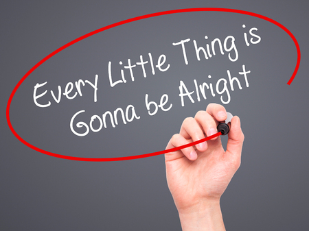 alright: Man Hand writing Every Little Thing is Gonna be Alright with black marker on visual screen. Isolated on grey. Business, technology, internet concept. Stock Photo