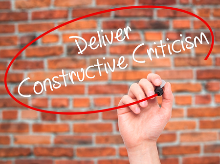criticism: Man Hand writing Deliver Constructive Criticism with black marker on visual screen. Isolated on background. Business, technology, internet concept. Stock Photo