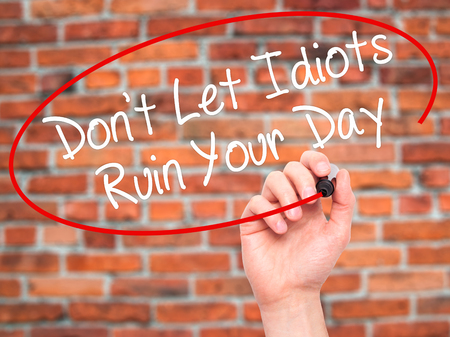 irrelevant: Man Hand writing Dont Let Idiots Ruin Your Day with black marker on visual screen. Isolated on bricks. Business, technology, internet concept. Stock Photo