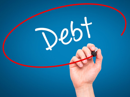 creditors: Man Hand writing Debt with black marker on visual screen. Isolated on blue. Business, technology, internet concept.