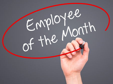 Man Hand writing Employee of the Month  with black marker on visual screen. Isolated on grey. Business, technology, internet concept. Stock Photo