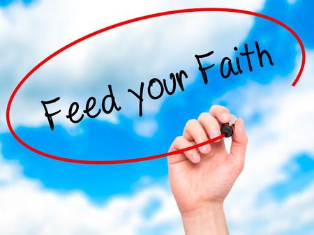 visual screen: Man Hand writing Feed your Faith with black marker on visual screen. Isolated on sky. Business, technology, internet concept. Stock Photo