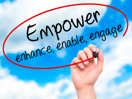 enable: Man Hand writing Empower enhance, enable, engage with black marker on visual screen. Isolated on sky. Business, technology, internet concept. Stock Photo