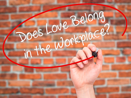 belong: Man Hand writing Does Love Belong in the Workplace? with black marker on visual screen. Isolated on bricks. Business, technology, internet concept. Stock Photo