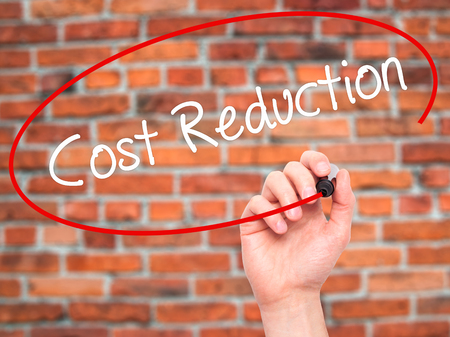 cost reduction: Man Hand writing Cost Reduction with black marker on visual screen. Isolated on bricks. Business, technology, internet concept. Stock Photo