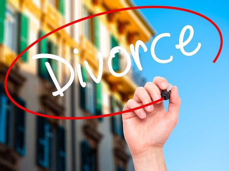 ex husband: Man Hand writing Divorce  with black marker on visual screen. Isolated on city. Business, technology, internet concept. Stock Photo