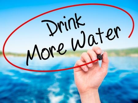living wisdom: Man Hand writing Drink More Water with black marker on visual screen. Isolated on nature. Business, technology, internet concept. Stock Photo Stock Photo