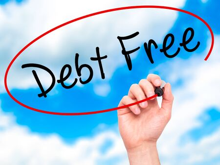 Man Hand writing Debt Free with black marker on visual screen. Isolated on sky. Business, technology, internet concept. Stock Photo
