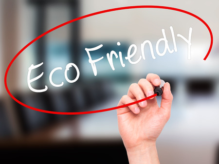 e systems: Man Hand writing Eco Friendly with black marker on visual screen. Isolated on background. Business, technology, internet concept. Stock Photo