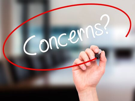 commenting: Man Hand writing Concerns? with black marker on visual screen. Isolated on office. Business, technology, internet concept. Stock Photo