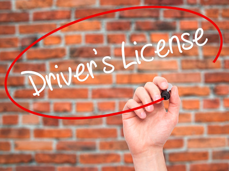 Man Hand writing Drivers License with black marker on visual screen. Isolated on bricks. Business, technology, internet concept. Stock Photo