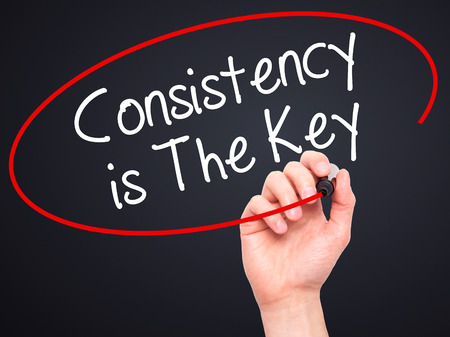 consistency: Man Hand writing Consistency is The Key with black marker on visual screen. Isolated on black. Business, technology, internet concept. Stock Photo