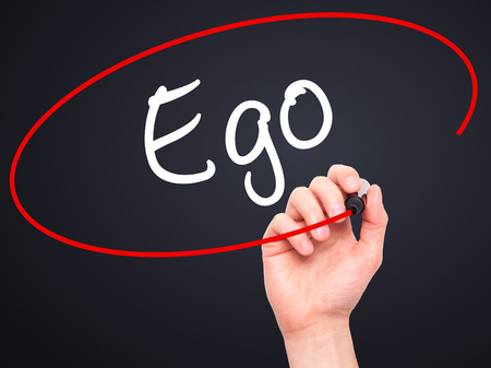narcissism: Man Hand writing Ego with black marker on visual screen. Isolated on background. Business, technology, internet concept. Stock Photo