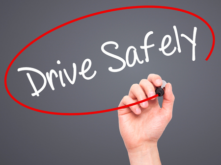 drive safely: Man Hand writing  Drive Safely with black marker on visual screen. Isolated on grey. Business, technology, internet concept. Stock Photo